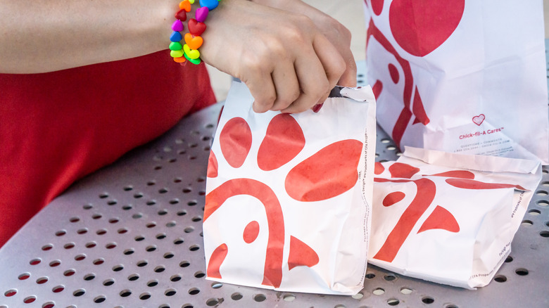 Hand with a rainbow bracelet holding a Chick-fil-a bag