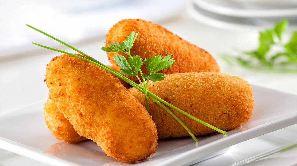 Four croquettes on a white plate