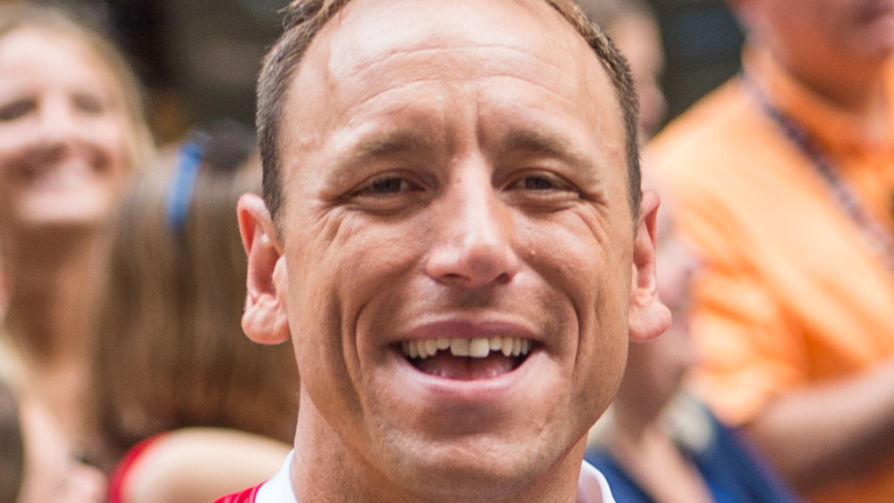 Closeup of Joey Chestnut smiling with people in background