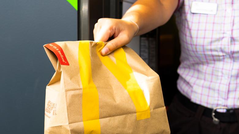 Employee handing bag at McDonald's drive-thru