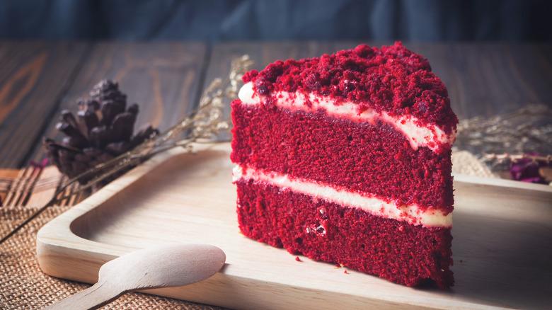 Slice of red velvet cake on wooden board