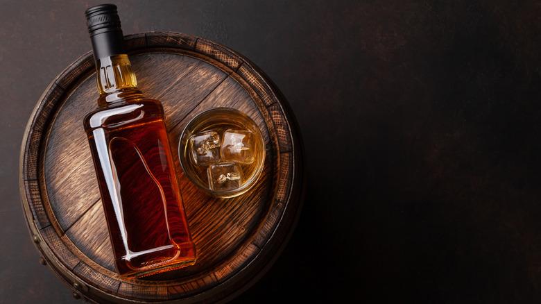 Bottle of Bourbon on top of a barrel