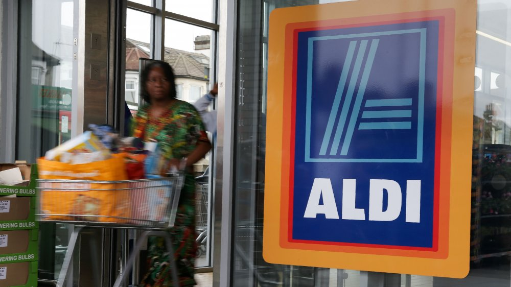 woman pushing a cart out of an Aldi store