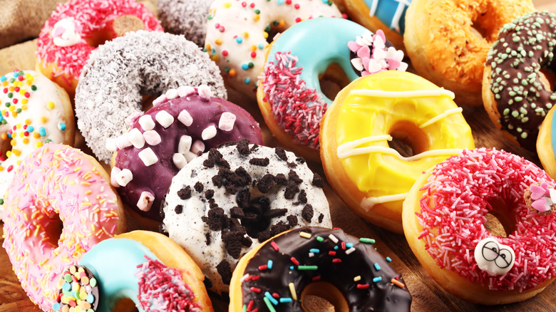 Assorted and colorful donuts on a wooden board