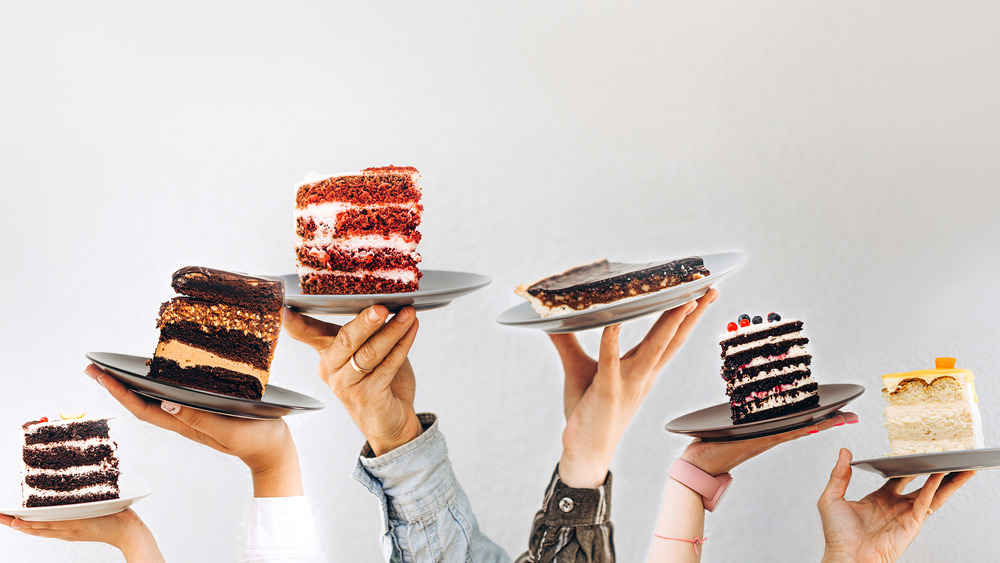 Hands holding up slices of cake