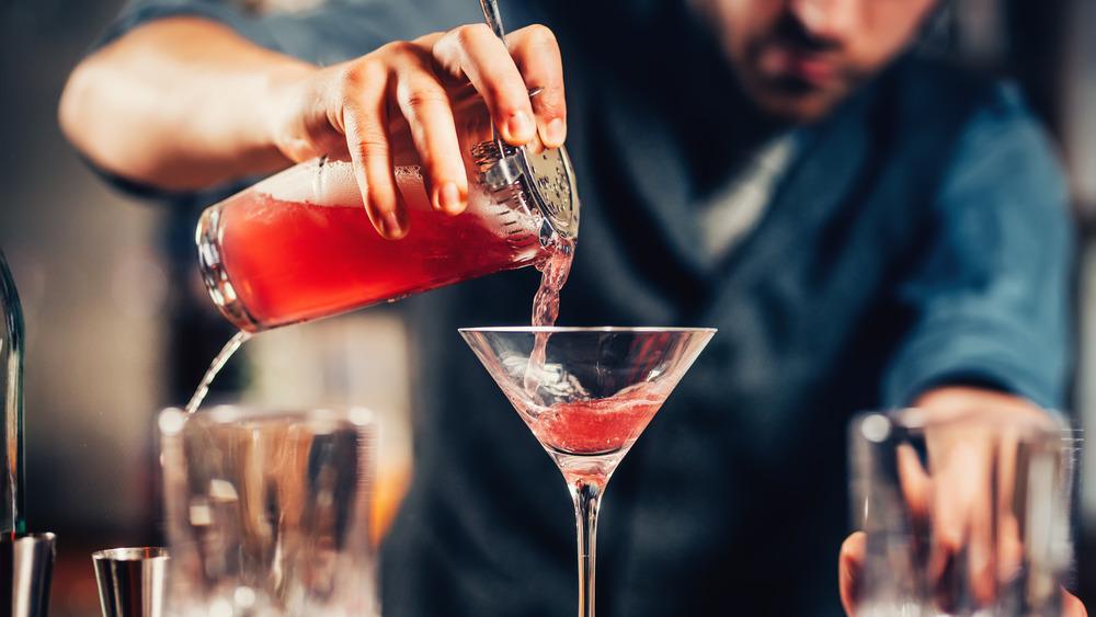 Person pouring a cosmopolitan into a glass