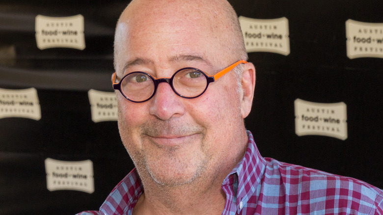 Andrew Zimmern wearing a plaid shirt and glasses