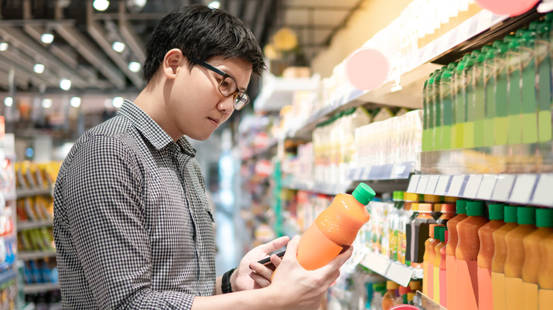 Man looking at carrot juice in grocery store