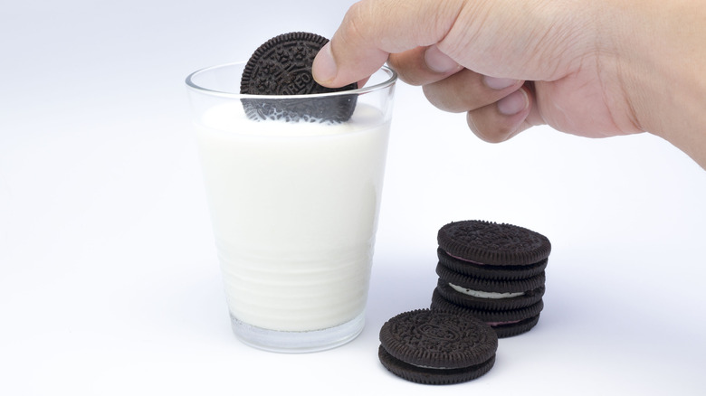Person dunking Oreos in a glass of milk