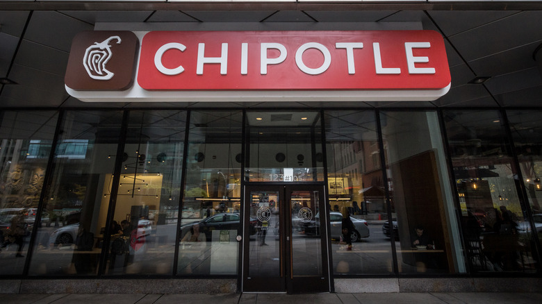 Red Chipotle sign on exterior of glass building