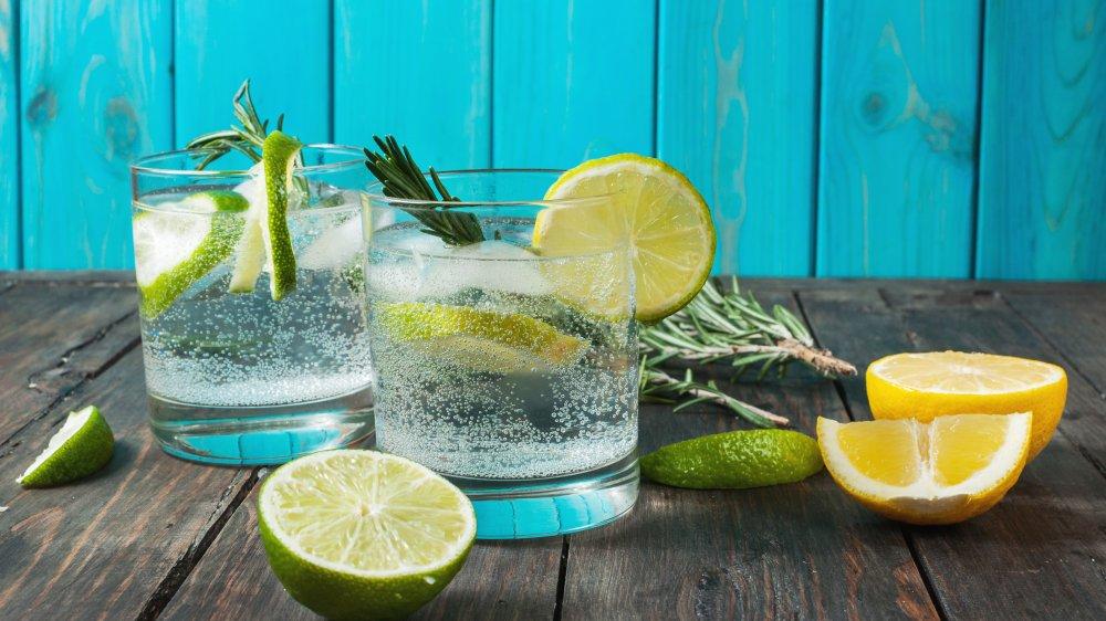 gin and tonics next to lemons and limes