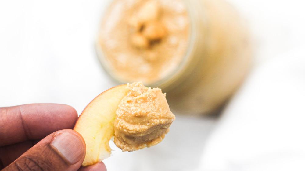 hand holding peanut butter on apple slice