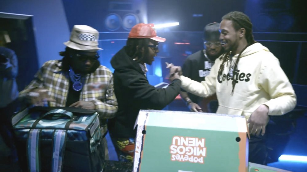 Migos with a box containing their collaboration meal with Popeyes