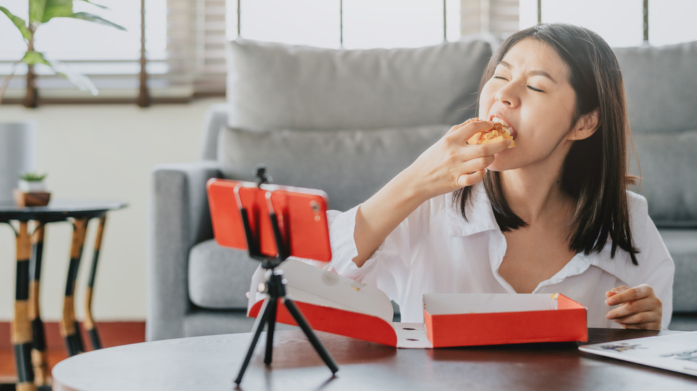 woman eating pastry on camera