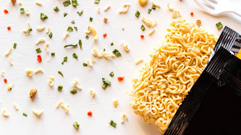 Ramen noodles in open black package with seasonings