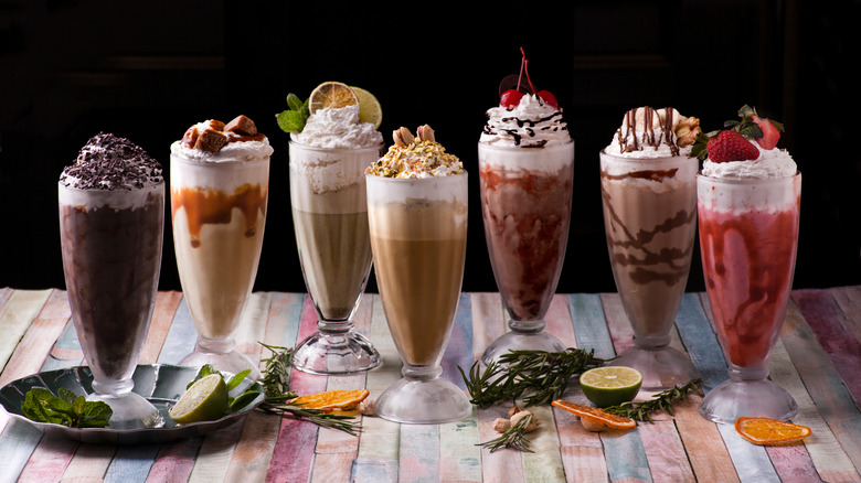 Variety of milkshakes lined up on a wooden table