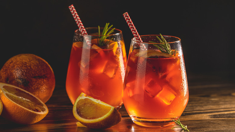 Two orange cocktails with fruit