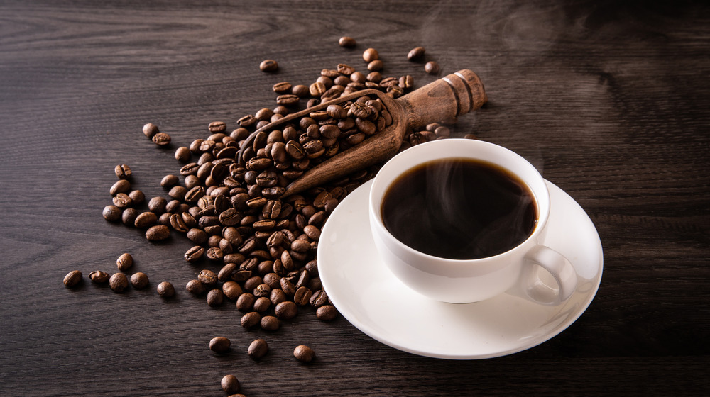 A cup of black coffee surrounded by coffee beans