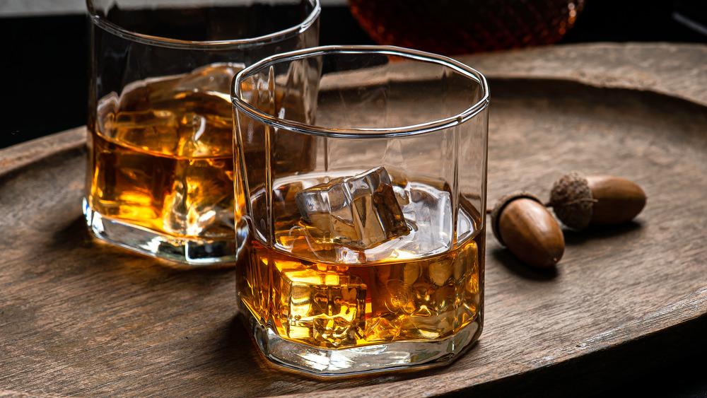 two glasses of bourbon with wood background