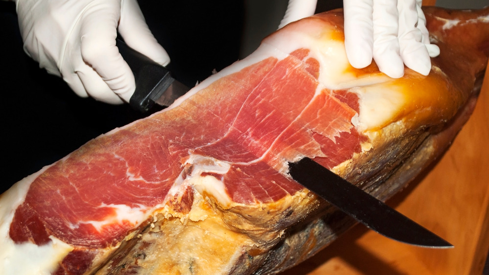 Leg of ham being sliced thinly