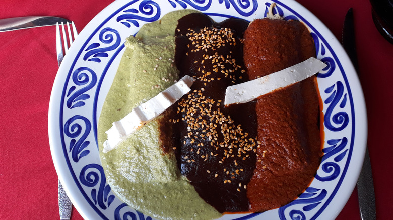 Green, black, and red mole varieties on a plate