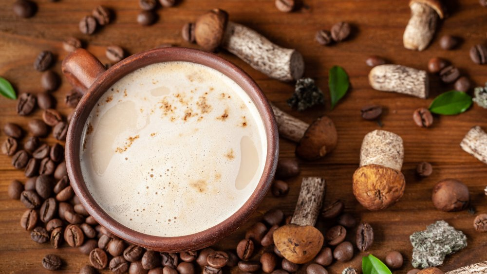 Cup of mushroom coffee surrounded by mushrooms and coffee beans