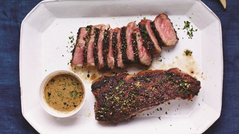 Peppercorn-crusted steaks on a white platter. There is a small bowl of cream sauce in the corner of the platter