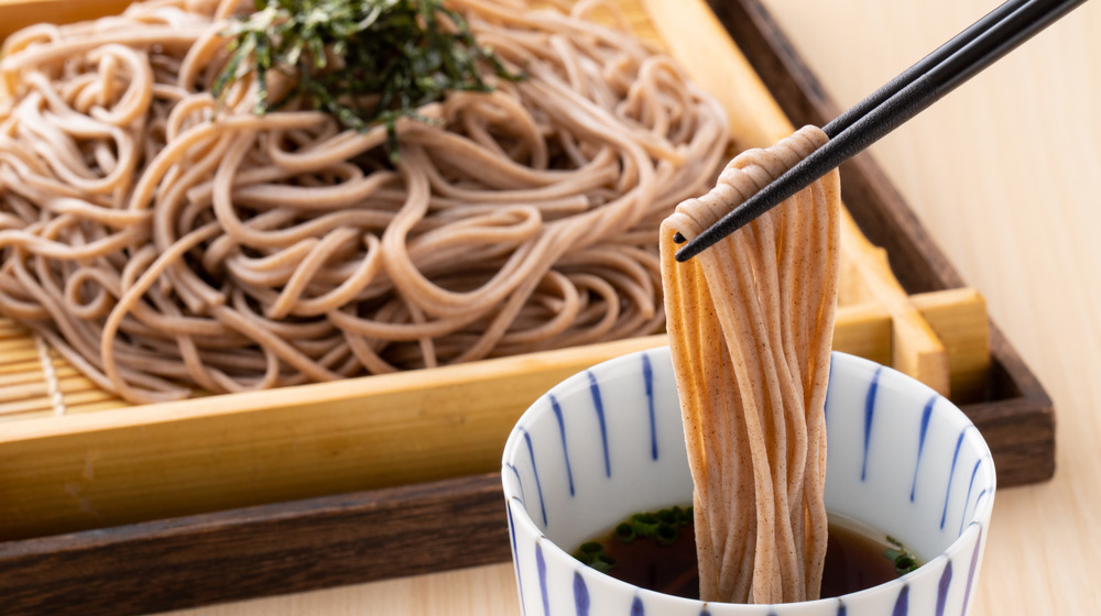 Soba noodles being dunked into broth