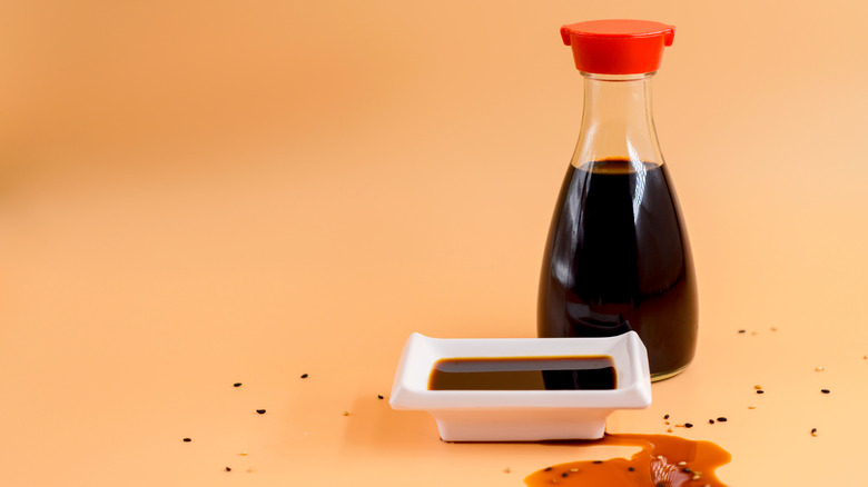 bottle of soy sauce with white dish of sauce