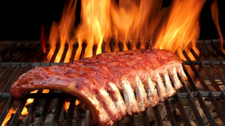 Babyback barbecued ribs on a hot charcoal grill.