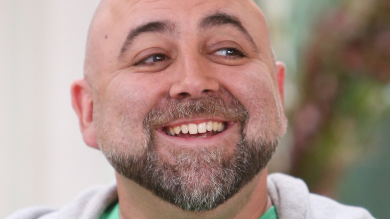 Duff Goldman smiles in hoodie and green shirt