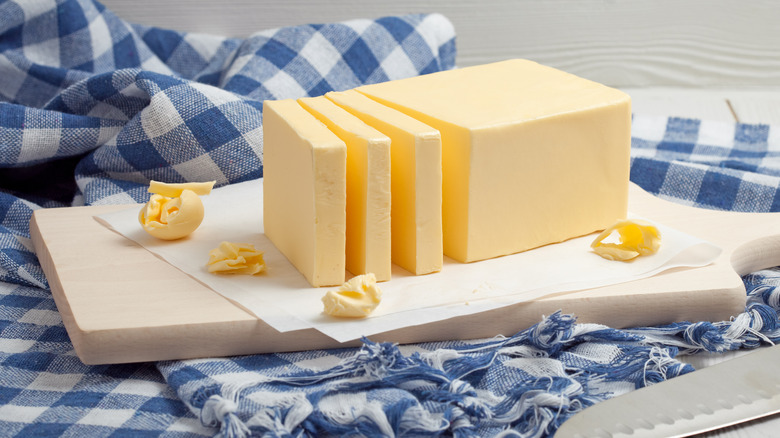 Stick of butter cut into chunks on wooden board