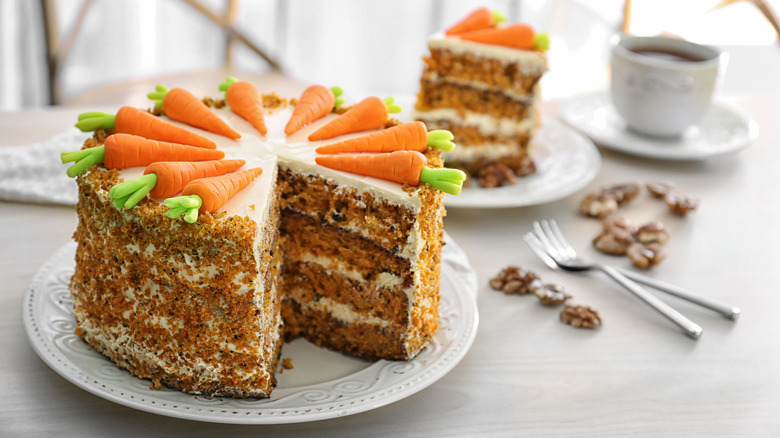 Whole carrot cake on white plate with slice cut out
