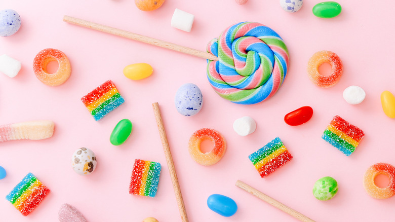 Lollipops, jelly beans, and various gummy candies on pink background