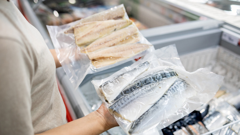 Packets of frozen fish in hands