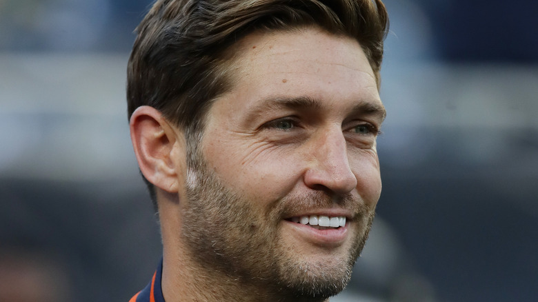 Jay Cutler smiles while watching a football game
