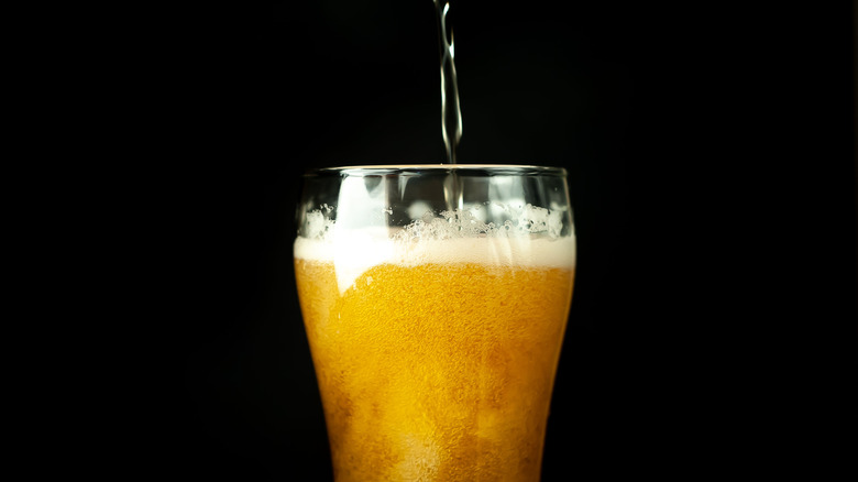 Glass of beer being poured against black background