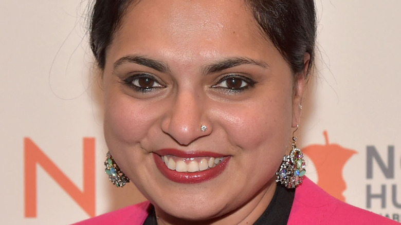Maneet Chauhan smiling in pink top and earrings