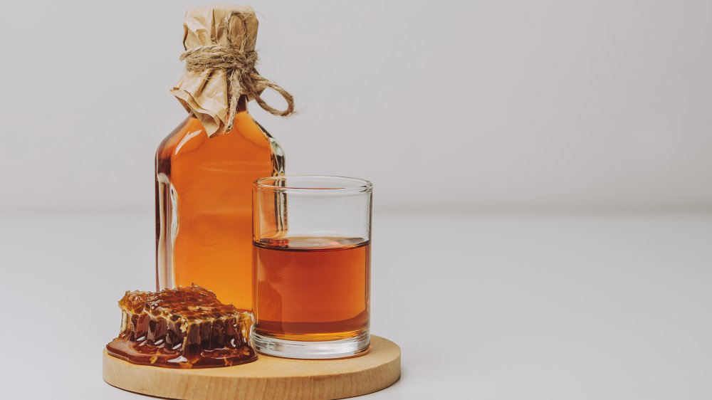 Mead on a board with a glass and honeycomb