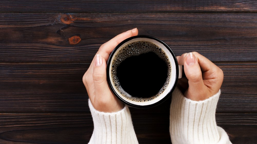 A generic image of a person holding a cup of coffee