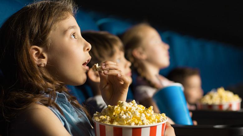 Kids watching movies, eating popcorn