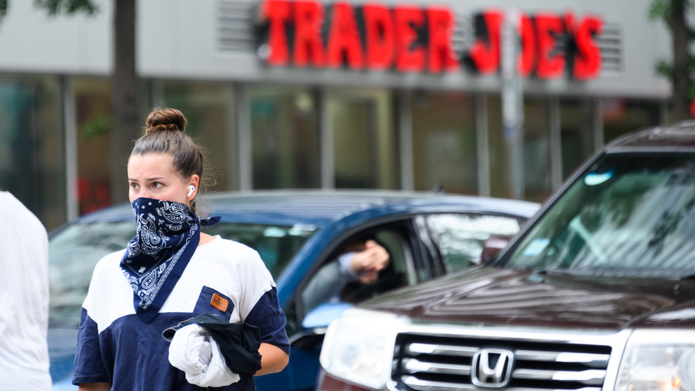 Woman wears face mask outside Trader Joe's