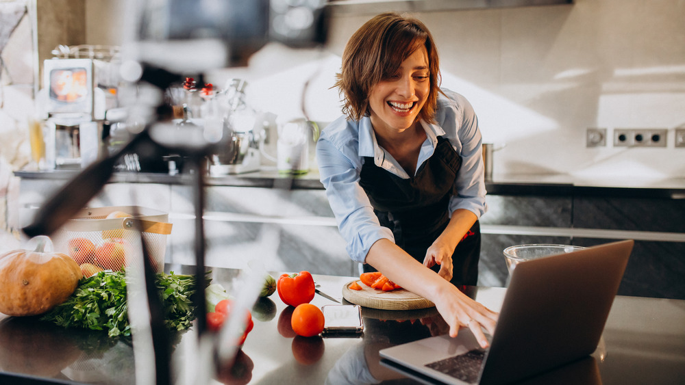 Woman cooking while blogging