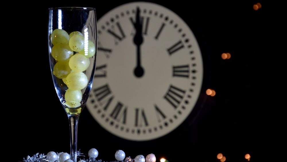 Champagne glass filled with grapes next to clock