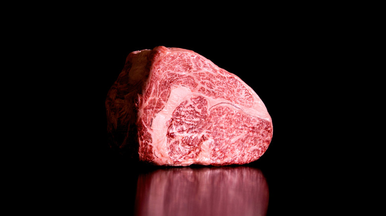 Red meat sitting on a black background