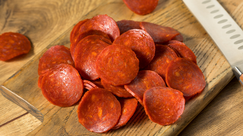 Pepperoni slices on wooden board