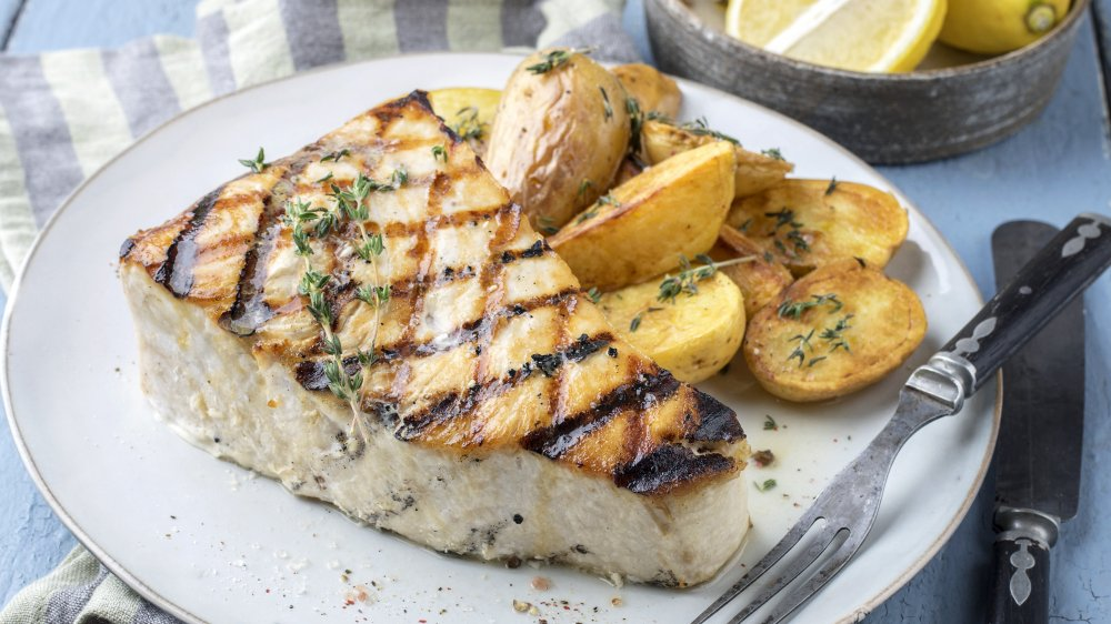 Thick piece of grilled swordfish on a white plate next to potatoes, twigs of thyme on top of both, a seafood fork is on edge of plate