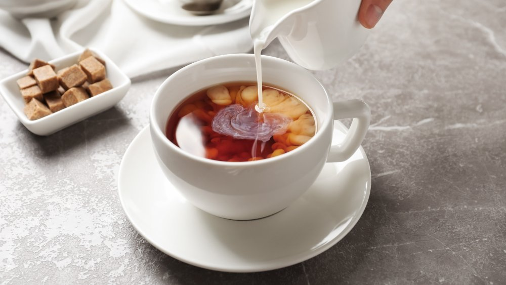 Milk being poured into a cup of tea