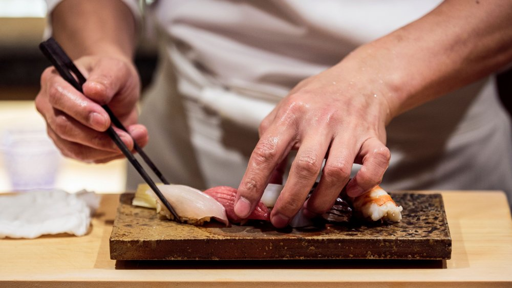 Male chef preparing sushi platter