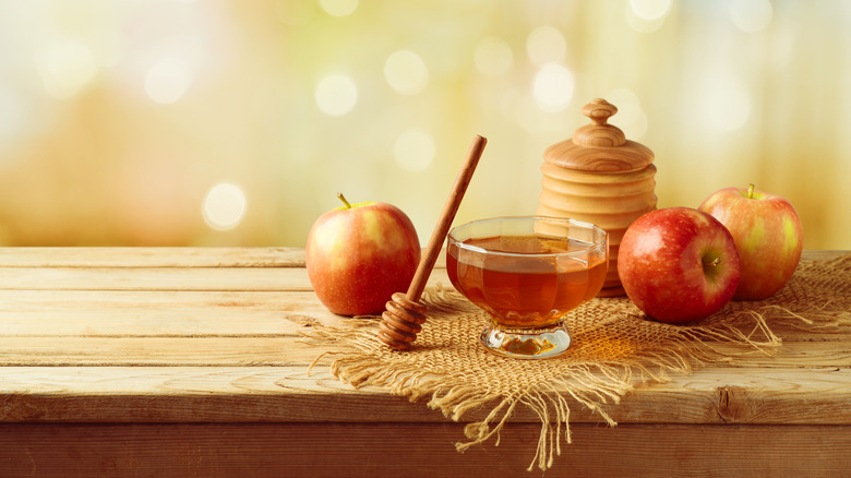 Apples and honey on wooden table
